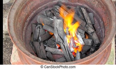 burning charcoal in metal rim