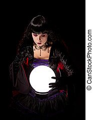 Attractive witch or fortune teller looking into a crystal...