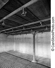 Bathroom with showers in concentration camp. In black and...
