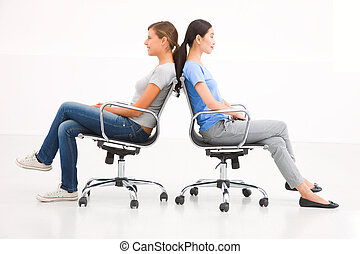 Two businesswoman sitting in chairs to back
