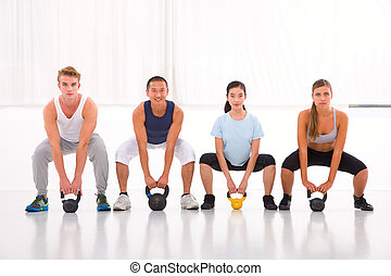 Multiethnic group of people doing kettlebell crossfit...