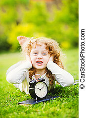 Little girl lying on the grass and covering her ears not to...