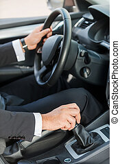 Driving a new car. Close-up of man in formalwear driving car...