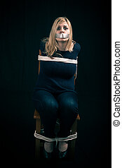 Kidnapped woman hostage with tape over mouth and tied up...