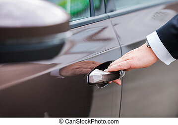 Hand on handle. Close-up of man in formalwear opening vehicle door