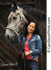 Beautiful young woman and gray horse portrait at the farm