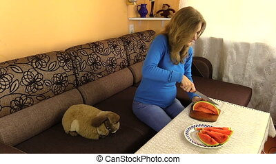 woman cut part watermelon - young pregnant woman cut slice...