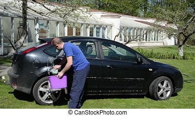 man bucket wash car - Man with bucket of soap water and...