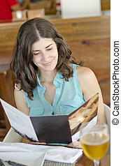 Woman reading restaurant card - WOman with cup of beer...