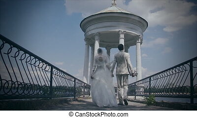 Newlyweds go over the bridge. Filming with a slider