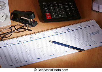 Date book on desck with calculator, glases, pen...