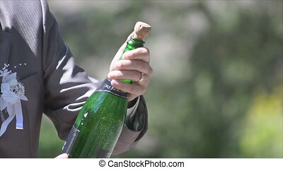 bottle of champagne openning - A man opens a bottle of...