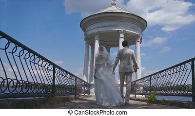 Newlyweds go over the bridge. Bride and groom holding hands....