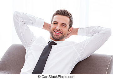 Taking time to relax. Happy young businessman in shirt and...