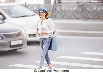 Crossing the street. - Happy young female student crossing...