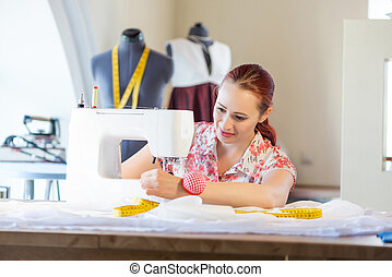 Seamstress at work - Young attractive needlewoman at studio...