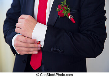 Hands of wedding groom getting ready in suit.