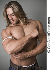A bodybuilder measuring the increase in his bicep