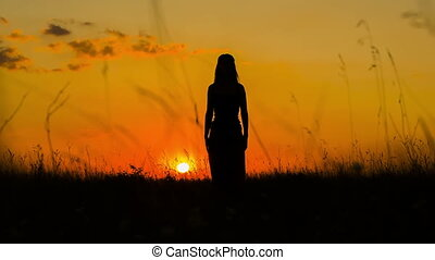 Silhouette of a Young Woman Practicing Yoga  At Sunset