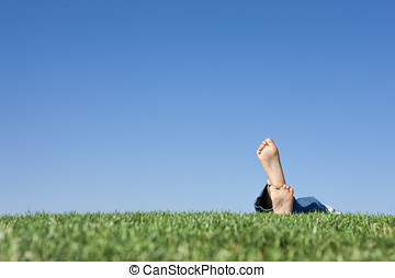 Feet, grass, sky - A conceptual image of the feet of a child...