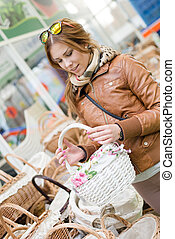 charming woman holding a basket in her hands looking smiling...
