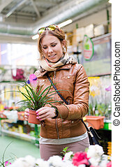 happy woman holding a pot in hand looking smiling in supermarket