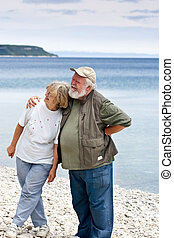 Two Seniors on the beach - Two seniors on a rocky beach. The...