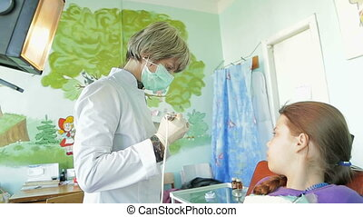Dentist Correcting Braces For Crooked Teeth - Girl watching...