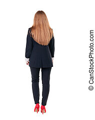 walking red head business woman. back view. going young girl...