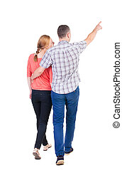 Back view of walking young couple (man and woman) pointing....