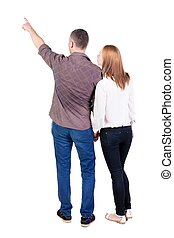 young couple pointing at wal Back view (woman and man). Rear...