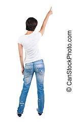 Back view of young brunette woman pointing at wall. beautiful gi