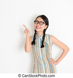Asian Chinese girl pointing on blank copy space