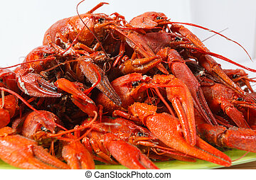 Boiled crayfish on green plate on a white background, a...