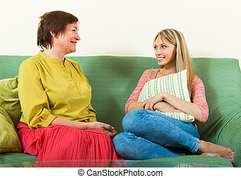 adult daughter and mother resting on sofa