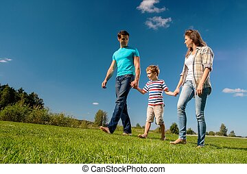 Happy young family with their child walking outdoors