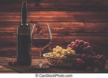 Bottle of red wine, glass and grape in basket in wooden...