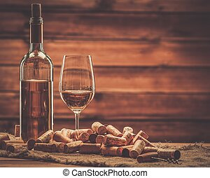 Bottle and glass of white wine on a wooden table among corks...
