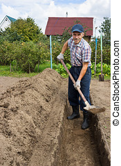 Farmer digging the earth to build  deep bed of
