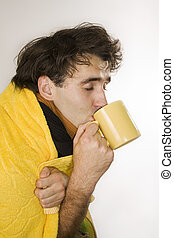 Flu - Young man drinks hot tea and hopes to become well
