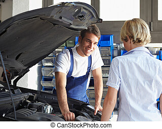 mechanic talking with female client in auto repair shop