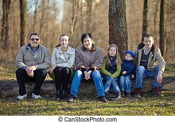 Big happy family portrait sitting on a big log in early...