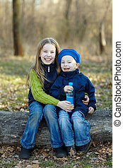 Two happy kids together with water bottle sitting on a big...
