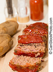 Sliced Meatloaf and Baked Potatoes on Wood Board - Sliced...