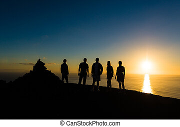 Group of travellers at sunset. View from top of La Palma...