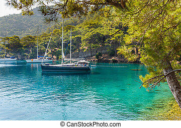 Sailing yacht at calm bay - Sailing yachts stay at anchor at...