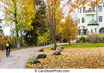 Autumn ciclyng - Men riding bicycle at colorful autumn park...