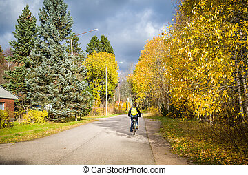 Autumn ciclyng - Woman riding bicycle at village road....