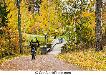 Autumn ciclyng in parks - Men riding bicycle at colorful...