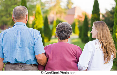 Elderly care - Elderly couple walking in the nature with the...